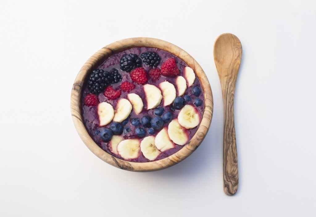 acai berry smoothie bowl in a wooden bowl on white background